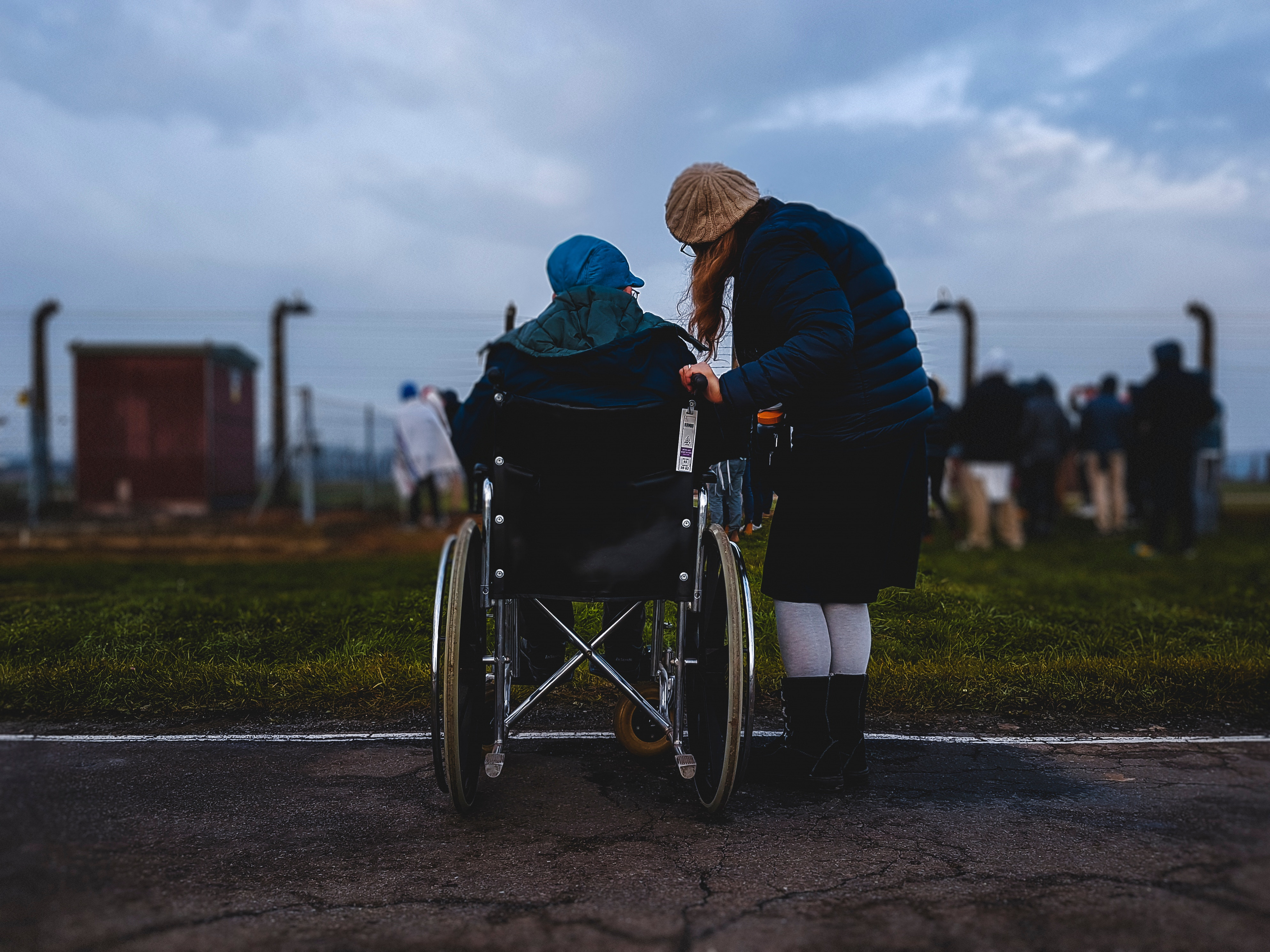 A picture of a woman holding another person who is seated in a wheel chair