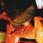 a picture of two women wearing orange kimonos facing away from the camera