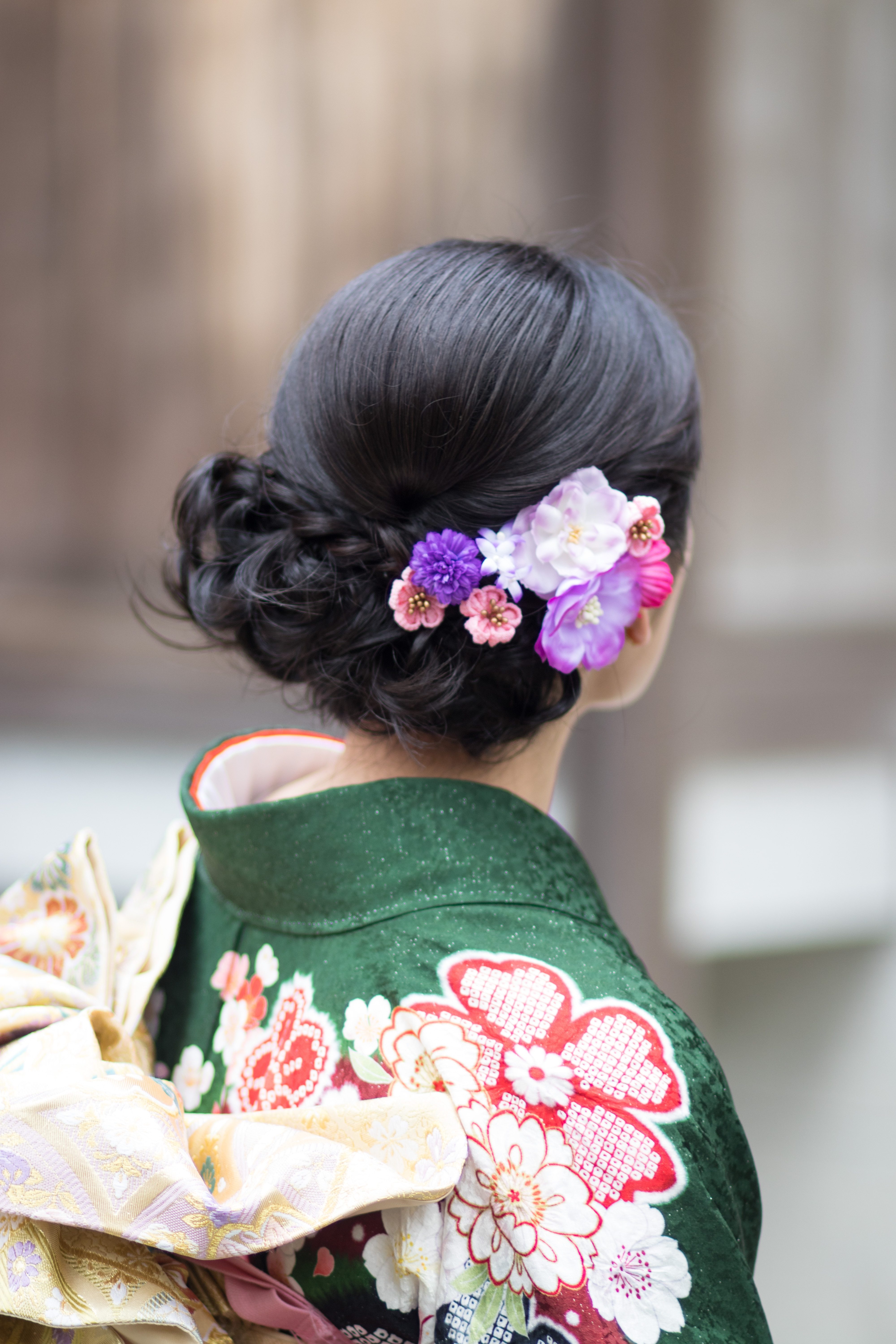 A woman in a green kimono with flowers in her hair